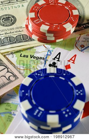 Las Vegas map, and money, poker chips and pair of aces playing cards. Vertical image.