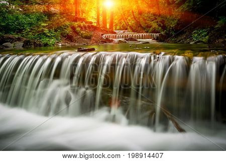nice landscape with sunshine over waterfall in forest