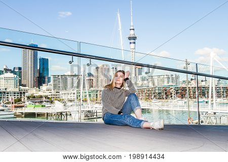 outdoor portrait of young happy smiling teen girl enjoying her trip to auckland, on city scape reflection background