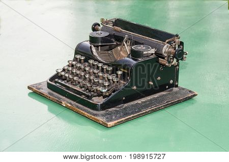 Old mechanical typewriter standing on a green plane.