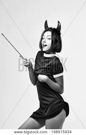 halloween woman or girl with smiling face in dress and devil horns or antlers holiday costume holds stick isolated on white background black and white