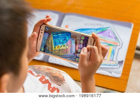 ZhongshanChina-August 8 2017:kid playing Augmented Reality popup paintings of a filled temple via mobile. AR and VR games become more and more popular.