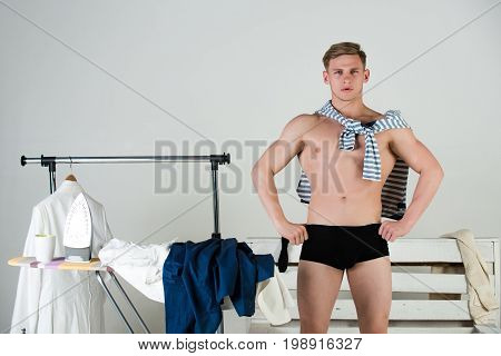 Man posing with hands on hips. Macho wearing underwear on muscular body on grey background. Ironing board with iron and clothes. Fit and fitness. Housework concept.
