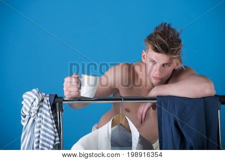 Man holding cup. Model in wardrobe or dressing room. Clothes hanging on rack. Fitness and fashion concept. Macho with muscular torso.