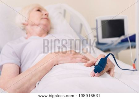 Professional equipment. Worried chronic sick lady recovering from a disease and having her pulse in check all the time while lying in hospital bed