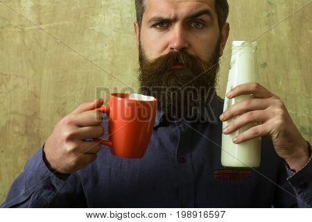 Hipster in shirt with yoghurt and cup. Dieting and health. Food and drink. Ecology product and glass. Man with long beard hold milk bottle.