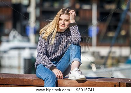 outdoor portrait of young happy smiling teen girl on marine background on a sunny day, auckland central wharf, new zealand