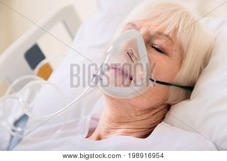 Easier to breathe. Vulnerable ailing aged woman lying in hospital and getting well while wearing oxygen mask during her sleep