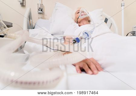 High quality services. Feeble chronic aged lady sleeping and recovering from lungs disease while the apparatus sustaining her breath