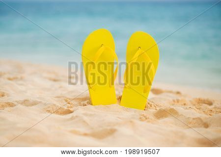 Yellow sandal flip flop on the white sand beach with blue sea and sky background in summer vacations copy space.