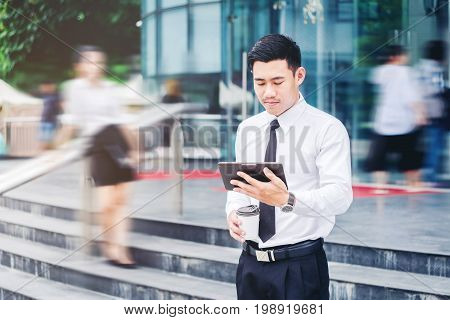 Businessman Using A Digital Tablet Office Outdoors And Blurred People Walking In Front Of Modern Off