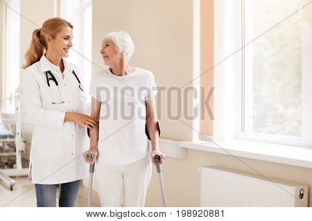 Back on track. Proficient attentive nice woman helping her patient walking again while she recovering from severe leg injury