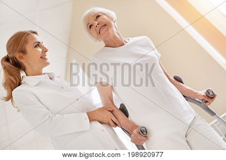 Benefits of optimistic approach. Focused cute aged lady recovering from leg injury and taking a walk using a pair of crutches and doctors support