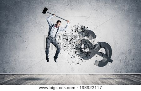 Young furious businessman crashing with hammer stone dollar symbol