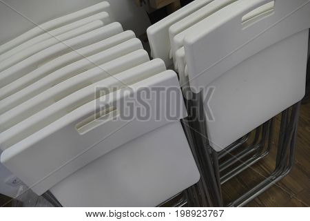 many stocked white stackable plastic chairs sacked