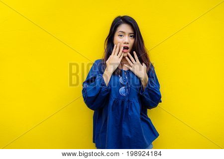 Young girl asian shocked product sale with glasses on yellow backgrond studio