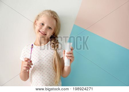 Cute girl with toothbrush and paste on color background. Teeth cleaning concept