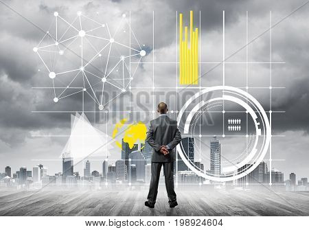 Back view of young businessman on city background with business icons and chart