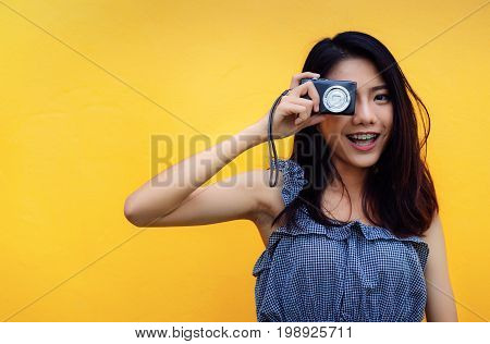 Young girl asian take a photo with compact camera on yellow background