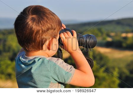 Boy looks through the binoculars. Little boy travel in nature and look into mountains