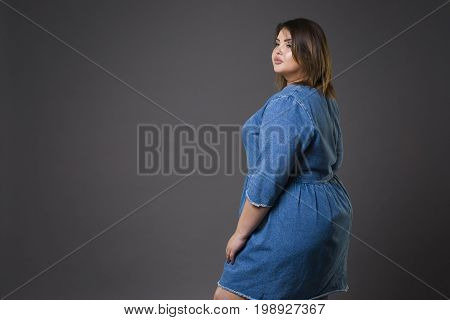 Plus size fashion model in casual jeans clothes fat woman on gray studio background overweight female body full length portrait