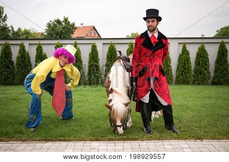 Gentleman with his pony and the clown
