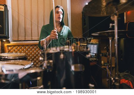 Drummer rehearsing before rock concert. Man playing drums in music recording studio