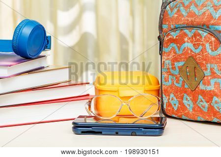 School Backpack With School Supplies. Books, Sandwich Box, Headphones, Glasses And Ebook On Wooden T