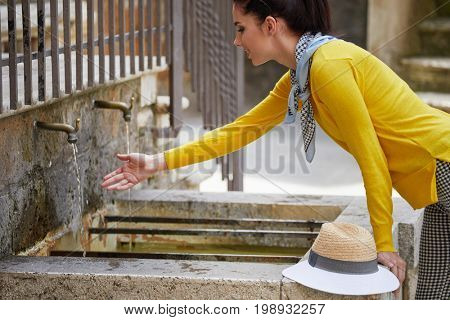 Young woman washing hands in a city fountain. Young woman drinking clean water from the tap in Italy