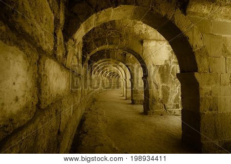 Internal passages in the ancient Roman amphitheater of Aspendos. The province of Antalya. Mediterranean coast of Turkey. Vintage toning. Stylization.