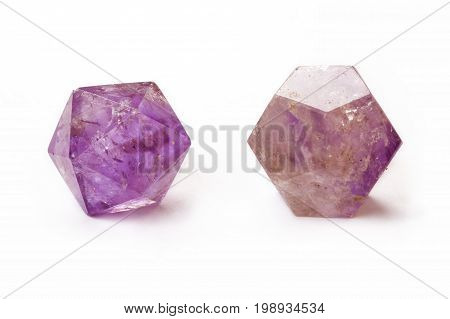 Amethyst dodecahedron and icosahedron isolated on a white background. Macro shot
