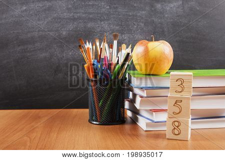 School supplies with a stack of books and an apple on blackboard background with copyspace for your text, design. Back to school concept for banner, promotion, web.