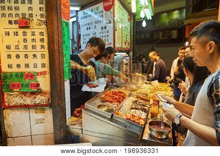 HONG KONG - DECEMBER 25, 2015: street food stall in Kowloon at night. Kowloon is an area in Hong Kong comprising the Kowloon Peninsula and New Kowloon.