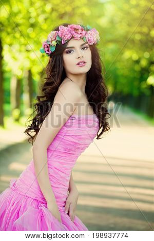 Beautiful Woman Fashion Model wearing Prom Dress with Flowers on Green Blurred Background Outdoors