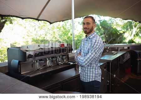 Portrait of male owner standing with arms crossed at outdoor café