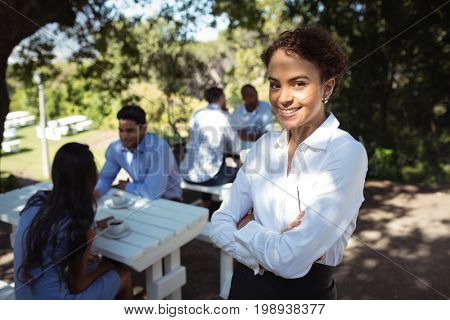 Portrait of waitress standing with arms crossed at outdoor restaurant