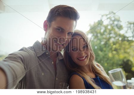 Portrait of smiling couple having champagne in restaurant