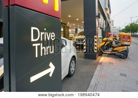 BUSAN, SOUTH KOREA - CIRCA MAY, 2017: Drive Thru sign at McDonald's. A drive-thru is a type of service provided by a business that allows customers to purchase products without leaving their cars.