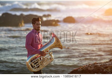 Musician with Tuba on the sea coast during surf. Romantic photo.