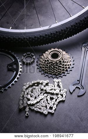 Bicycle parts and tool on gray background