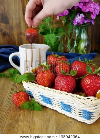 Strawberries in a wicker basket and chocolate sauce in a ceramic jug. Female hand is dipping strawberry into the sauce