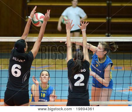 KAPOSVAR, HUNGARY - JANUARY 23: Zsanett Pinter (R) strikes the ball at the Hungarian NB I. League woman volleyball game Kaposvar vs Miskolc, January 23, 2011 in Kaposvar, Hungary.