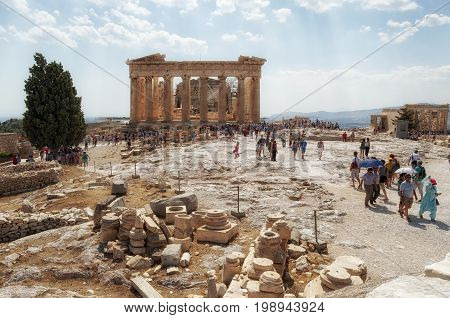 Editorial Parthenon, Greece - July 04, 2013: Tourists throng around the Parthenon situated on a high rocky outcrop in Athens, a former temple at the Acropolis, Greece, dedicated to the goddess Athena