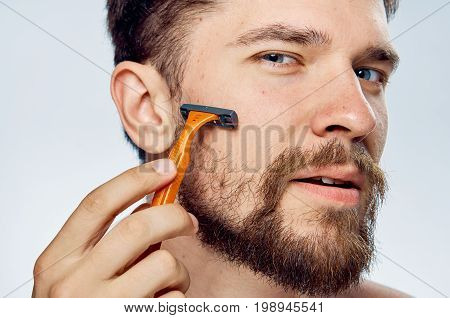 Man with a beard on a light background shaves with a razor, portrait.