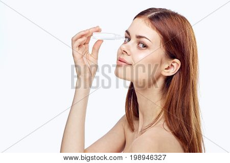Beautiful young woman burying her eyes on a white background, pharmacy.