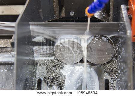 The band saw machine cutting the steel rod with the coolant