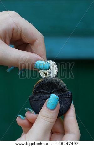 A small black purse and a coin in the hands of a girl