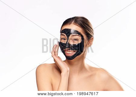 Beautiful young woman on white isolated background in a coal cosmetic face mask, smile.