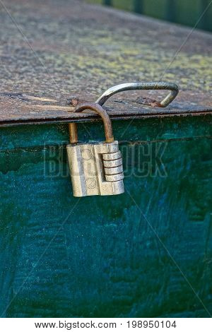 Code padlock on an old iron tank