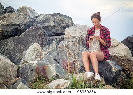 A beautiful dark-haired woman in a plaid shirt denim shorts white sneakers knits with knitting needles a gray sweater made of natural woolen thread a sweater and sits on the stone rocks near the sea